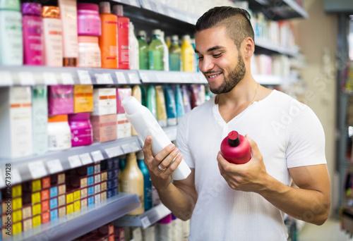 Fotografie, Obraz  Man selecting shampoo in the store.