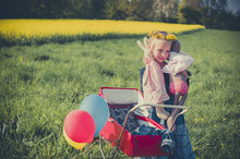 Smiling Little Girl Holding Doll And Soft Toy Standing On Meadow With Doll Carriage