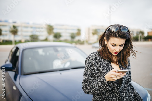 Spain, Cubelles, young woman sitting on the hood of the car looking at her smartphone