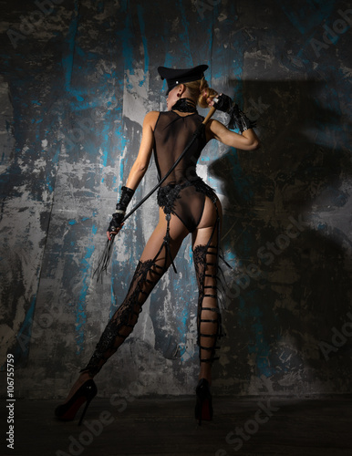 Fotografering  Girl in a cap, in beautiful lingerie with a whip stands near the wall