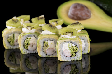 Fototapeta Sushi Sushi Roll with crab meat, kiwi and avocado over black backgrou