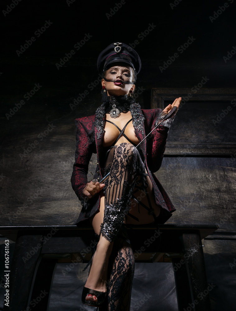 Fotografering  Girl in a beautiful cap and a jacket standing near the wall with a whip