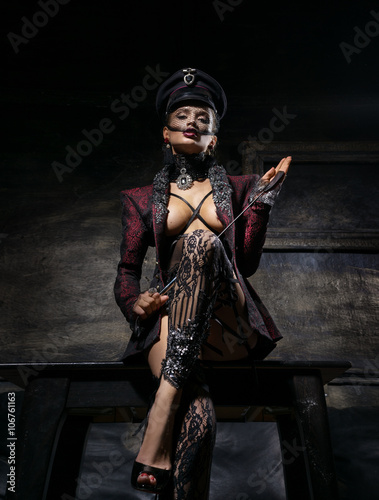 Photo  Girl in a beautiful cap and a jacket standing near the wall with a whip