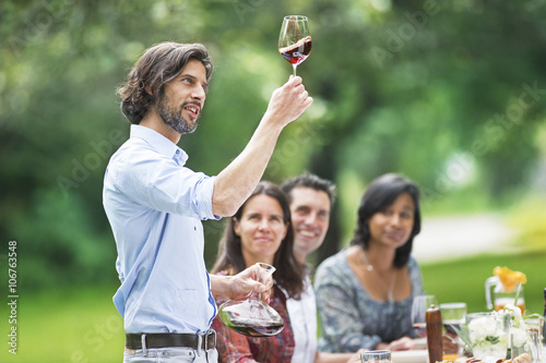 Man tasting red wine on a garden party