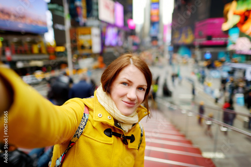 Plagát  Beautiful young woman taking a selfie with her smartphone on Times Square