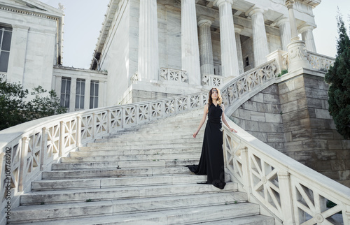 young lady in black dress on stone stairs Wallpaper Mural