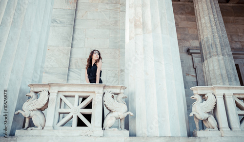 Photo  young lady in black dress on stone balcony