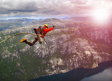 Young Man Jumping From A Cliff...