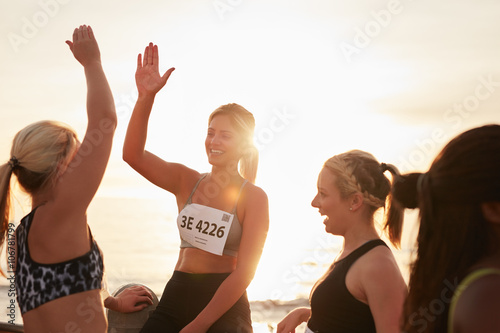 Fotografia  Female runners high fiving each other after a race