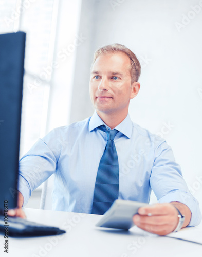 businessman with calculator, computer and papers