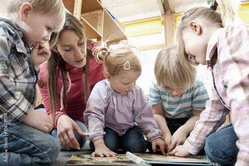 Female educator and four kids looking at picture book
