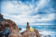 A girl sits on a rock on the beach against the sky and the sea, lifestyle, recreation, solitude, meditation