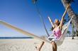 femme heureuse dans un hamac à la plage avec un ordinateur portable