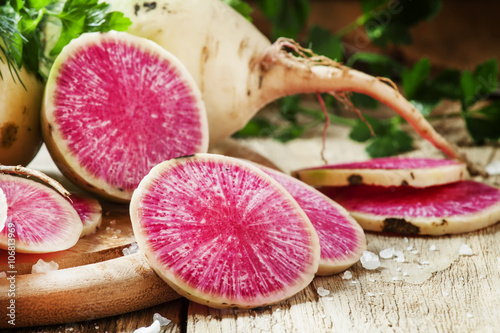 Slices of pink watermelon radish on a wooden table with parsley