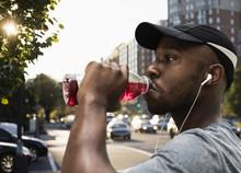 Black Runner Drinking Juice In City