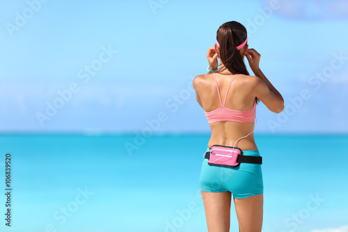 Fotografía  Chica corredor de fitness está preparando para la ejecución en playa escuchando música con auriculares y soporte de teléfono inteligente correa de cintura riñonera como ropa deportiva que llevan portátil rastreador de actividad de tecnología