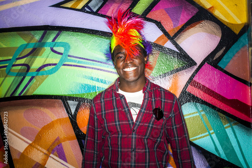 Black man in colorful wig smiling near graffiti wall Poster