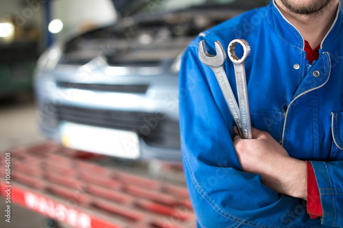 Vászonkép Hand of car mechanic with wrench. Auto repair garage.