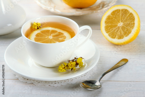 Fototapety, obrazy: a Cup of fragrant green tea and an iron spoon with lemon on wooden background