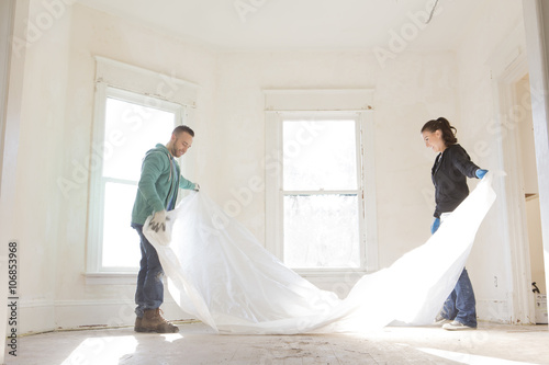 Mixed race couple spreading tarp in new home Plakat