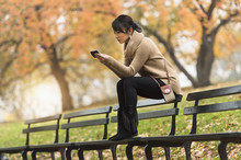Asian Woman Using Cell Phone On Park Bench