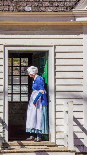 Fotografie, Obraz  Senior woman in Colonial Williamsburg in traditional english blue dress standing
