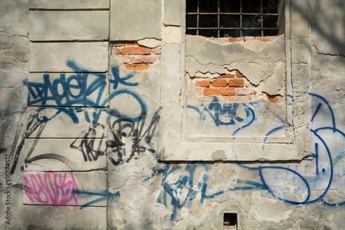 Stara zniszczona ściana z napisami graffiti - fototapety na wymiar