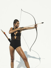 Mixed Race Woman Aiming Bow An...
