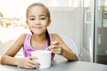 Mixed Race Girl Eating Ice Cream At Outdoor Cafe