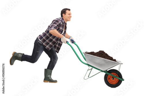 Gardener pushing a wheelbarrow full of dirt Wallpaper Mural
