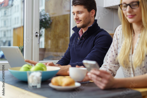 Foto  Paar sitzt nebeneinander am Tisch und schaut auf Notebook und handlich