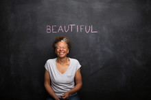 Senior Woman In Front Of Blackboard And The Word Beautiful