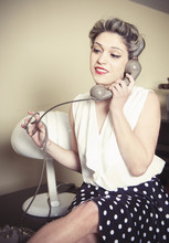 Portrait Of Young Woman Wearing Vintage Clothes And Talking On Vintage Phone