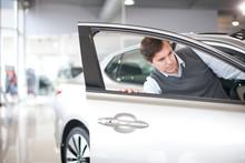 Mid Adult Man Checking Door In Car Showroom