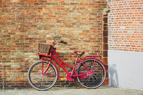Red bicycle against brick wall in Brugge