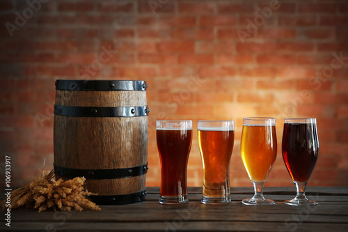 Fényképezés  Glasses with different sorts of craft beer, wooden barrel and barley ears on bri