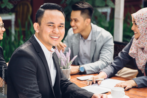 Valokuva  handsome businessman smiling at the camera