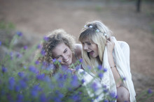 Two Teenage Girls Looking At Wildflowers In Woodland