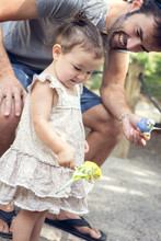 Father And Baby Daughter Holding Budgerigar Parakeets At Zoo