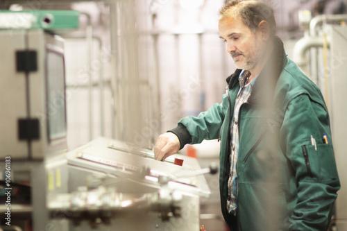 Brewery worker operating machine
