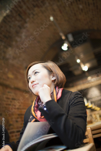 Young woman daydreaming with book