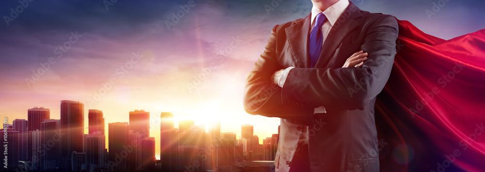 Fototapeta Businessman Superhero With Red Cape Dominates The City