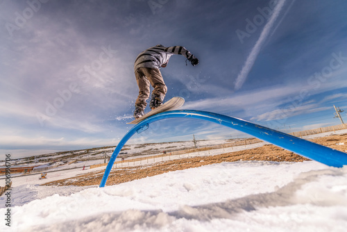 Photo  Snowboarder sliding on a rail