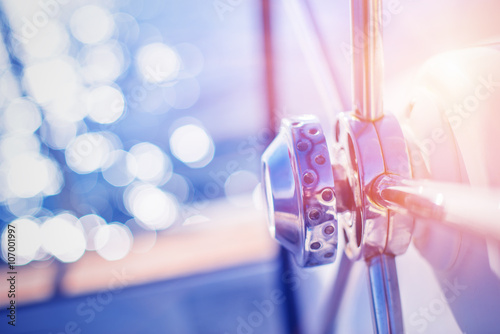 Fototapeta Yachting detail - Rudder on deck / board with water and sun reflection in background obraz