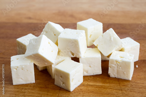 Square cubes of feta cheese isolated on wood board.
