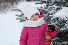 Little Girl With Winter Clothes Holding Red Lantern Near Fir Tree In Snowy Park Outdoor