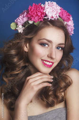 Deurstickers Akt Beautiful young girl with a floral ornament in her hair on a blue background. Woman in wreath of flowers.Beauty Face. Fashion photo.Perfect makeup. Skin care concept.