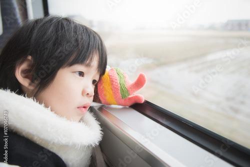 Fotografie, Tablou  Happy asian child looking out train window outside