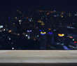 Empty wooden table in front of blurred light city tower, for you