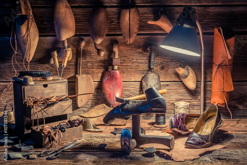 Vintage shoemaker workplace with brush and shoes